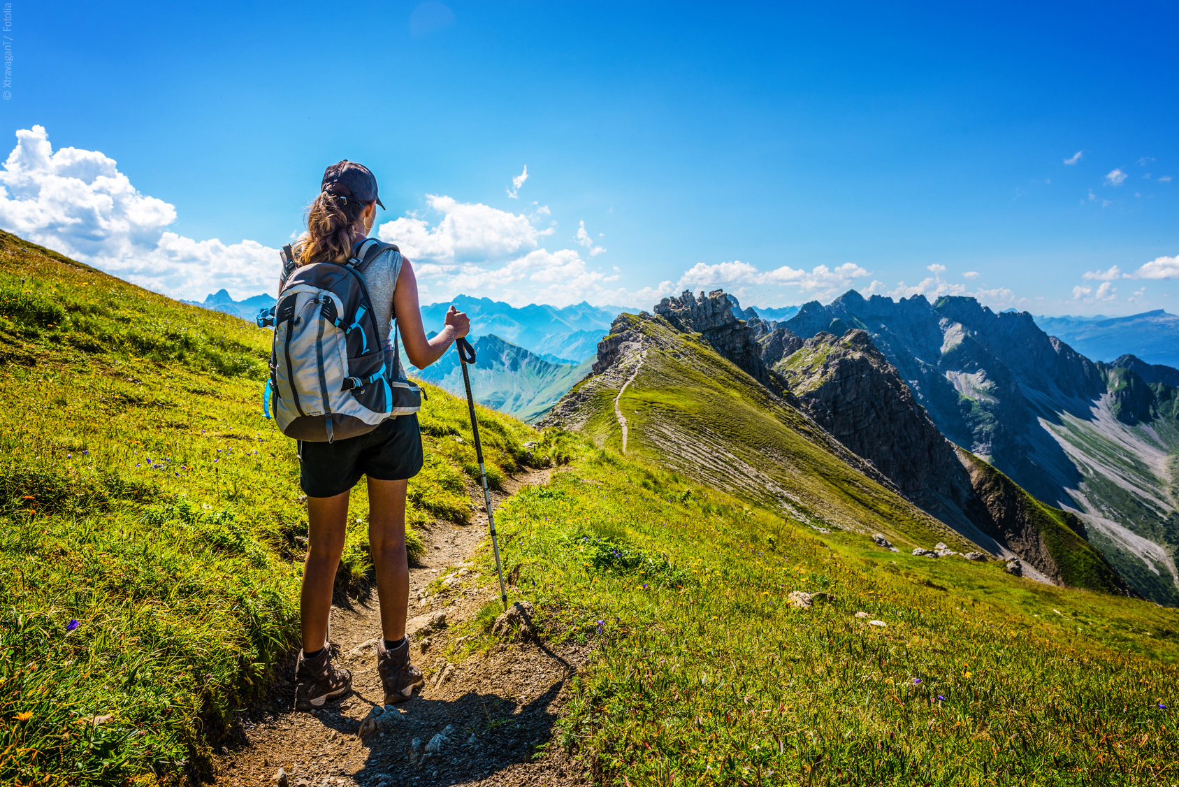 Female German hiker holds walking stick as she pauses on dirt mountain pass